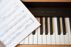 Piano keyboard and music book Royalty Free Stock Photo