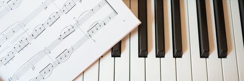Piano keyboard and music book Stock Photos