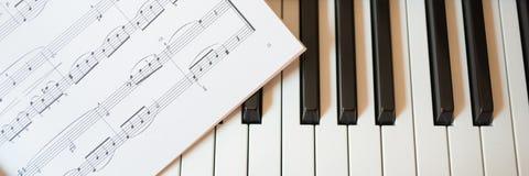 Piano keyboard and music book Stock Photos