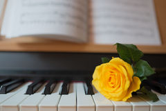 Piano keyboard with music book and yellow rose Stock Photography