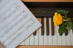 Piano keyboard with music book and yellow rose Stock Photos