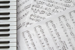 Piano keyboard on music-notes background. Top view royalty free stock images