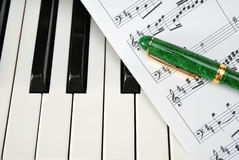 Piano keyboard with music score and pen Stock Photo