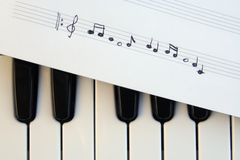 Piano keyboard and musical notes. Musical notes on a piano keyboard stock photography