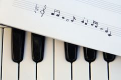 Piano keyboard and musical notes. Musical notes on a piano keyboard royalty free stock photo