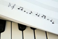 Piano keyboard and musical notes. Musical notes on a piano keyboard stock photo