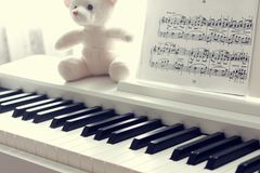 Piano keyboard , notes and toy closeup. Selective focus stock photo