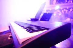 Piano keyboard. Being shined by purple light in the club royalty free stock photos