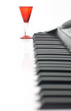 Piano keyboard and red glass Royalty Free Stock Photography