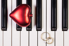 Piano keyboard,red heart and wedding rings Stock Image