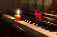 Piano keyboard with ribbon and burning candle Stock Photo