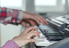 Piano Keyboard side View and Hands of Child and Mother Royalty Free Stock Image