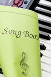 Piano keyboard with song book close up Stock Images