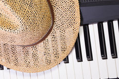 Piano keyboard and straw hat Royalty Free Stock Images