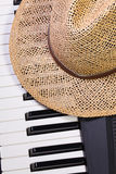 Piano keyboard and straw hat Stock Images