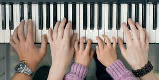 Piano Keyboard top View and Hands of Child Mother and Father Stock Photo