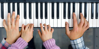 Piano Keyboard top View and Hands of Child Mother and Father. Family Unity Concept Image - Piano Keyboard top View and Hands of Child Mother and Father playing Stock Photo