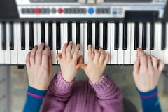 Piano Keyboard top View and Hands of Child and Mother Royalty Free Stock Image
