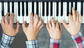 Piano Keyboard top View Hands of Man and Woman playing. Teamwork Concept Image - top View of Piano Keyboard and male and female Hands playing music together four royalty free stock photos