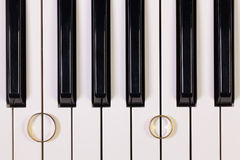 Piano keyboard and wedding rings Stock Images