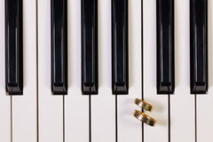Piano keyboard and wedding rings Royalty Free Stock Photos