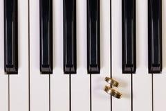 Piano keyboard and wedding rings Royalty Free Stock Photos