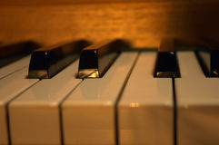 Piano Keys. Close-up shot of a piano lit by the golden afternoon sun Royalty Free Stock Photo