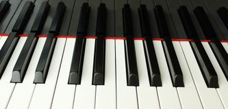 Piano Keys. The beautiful glossy finish of the white ivory and black piano keys with a little bit of the red felt stock image