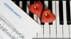 Piano keys with candles. Piano keys with two heart-shaped candles and sheet music (Wedding March Royalty Free Stock Image