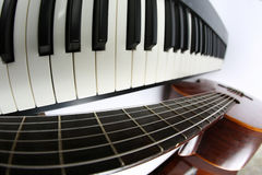 Piano keys and classical guitar close up on white background Stock Photos