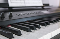 Piano keys closeup. Electric piano closeup of the keyboard and knobs. In the background you can see a sheet of musicpaper Royalty Free Stock Photos