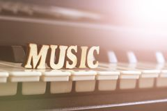 Piano keys closeup with the letters music. Object Stock Photo