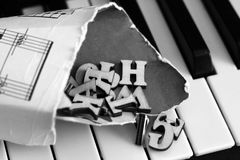 Piano keys closeup with wooden letters. Object Royalty Free Stock Photos