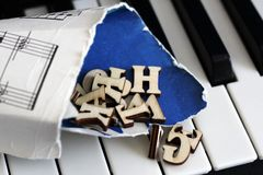 Piano keys closeup with wooden letters. Object Stock Image