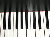 Piano keys - Duet of a life. Keys of a piano it is black white a red material / a thin asymmetrical strip and patches of light Royalty Free Stock Photography
