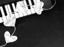 Piano keys and hearts of the music on a black background Stock Photos