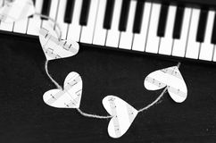 Piano keys and hearts of the music on a black background Royalty Free Stock Photo