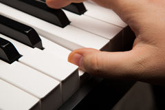 Piano keys and human finger Stock Image