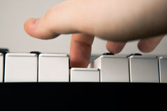 Piano keys and human finger Royalty Free Stock Image