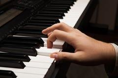 Piano keys and human hand Stock Photos