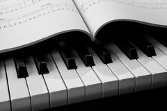 Piano keys and musical book. Black and white keys of the piano closeup and musical book Stock Photos