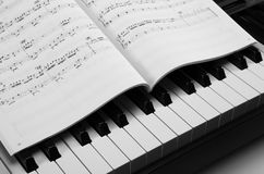 Piano keys and musical book. Black and white keys of the piano closeup and musical book Stock Image
