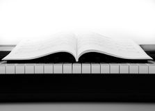Piano keys and musical book. Black and white keys of the piano closeup and musical book Royalty Free Stock Images