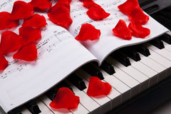 Piano keys and musical book. Black and white keys of the piano closeup and musical book with rose petals Royalty Free Stock Image