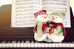 Piano keys and snowman doll.