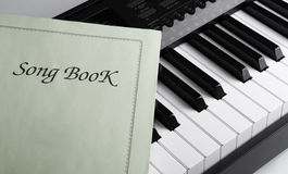 Piano keys and song book. Black and white keys of the piano closeup and song book Stock Photos