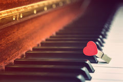 Piano keys with wooden red heart clip, vintage retro color style. Selective focus on the red heart clip Stock Photography