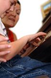 Piano lesson. Piano teacher and student during a lesson. The student's hands are the point of focus stock photography