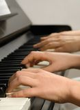 Piano lesson. Four hands playing on the piano keys while the teacher gives the student a lesson Stock Photo