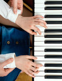 Piano lesson. Woman teaching little girl to play the piano. Top view Royalty Free Stock Photos